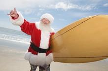 Santa Claus Gesturing With Surf Board On Beach