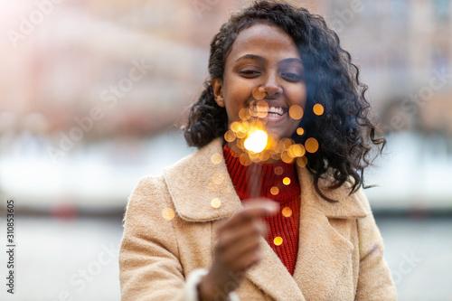 Fotomural  Happy woman at Christmas holding burning sparkler
