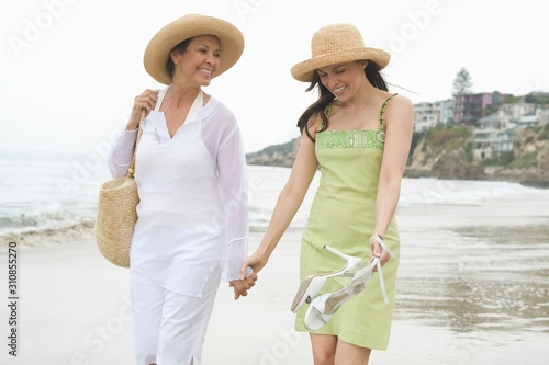 Fotografie, Tablou  Mother And Daughter Holding Hands While Walking At Beach