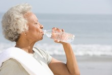 Senior Woman Drinking Water From Bottle At Beach