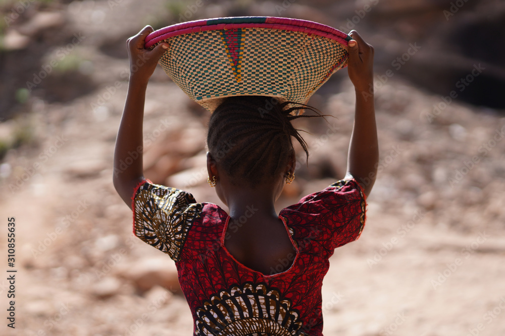 Fototapeta Candid Picture of Ethnic African Schoolgirl with Colorful Shirt and Basket