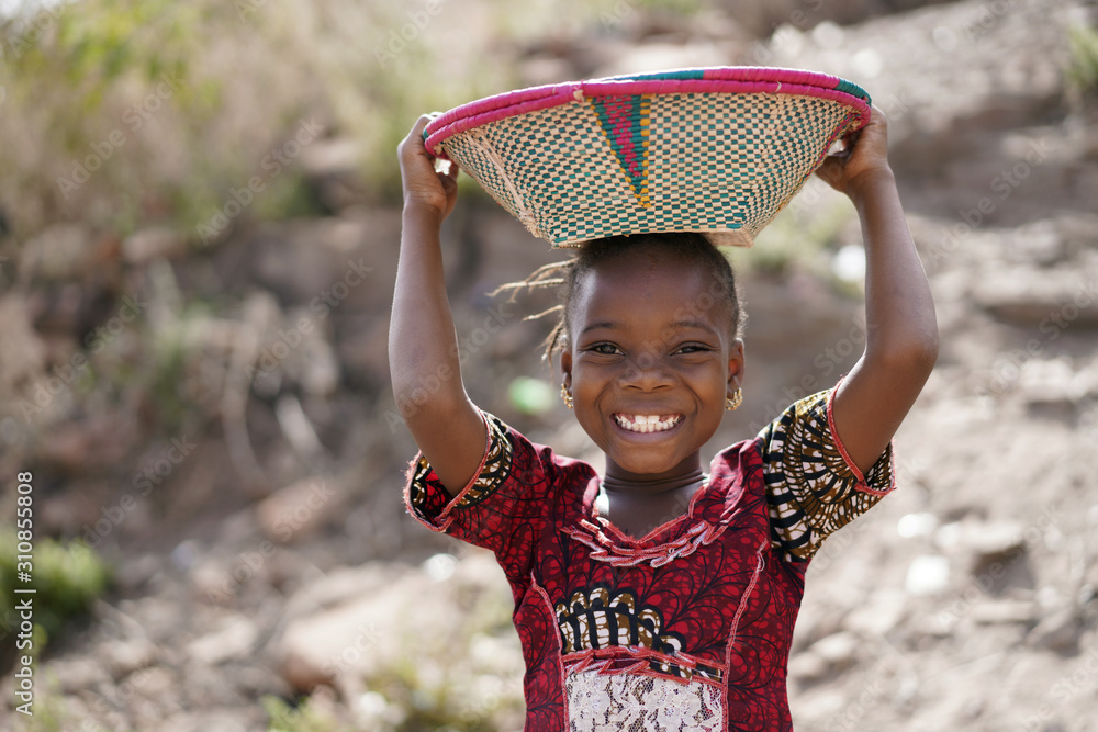 Fototapeta Body Shot of Cute African Young Girl Carrying Food Basket and Blurred Background