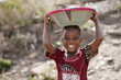 Leinwanddruck Bild - Body Shot of Cute African Young Girl Carrying Food Basket and Blurred Background