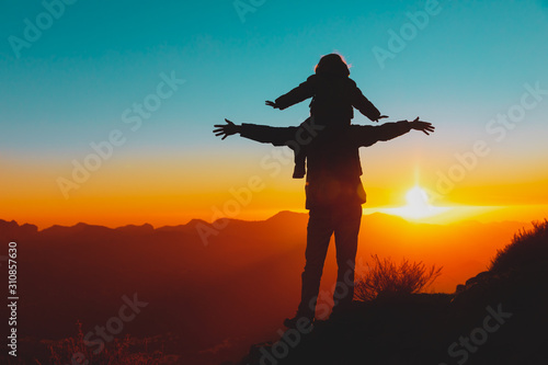Fotografija happy father and daughter travel in mountains at sunset