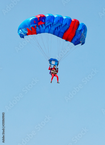 A paratrooper in a red suit descends under the canopy of a parachute Wallpaper Mural