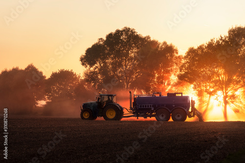 Tractor fertilizing agricultural field at sunset. Agriculture Canvas Print