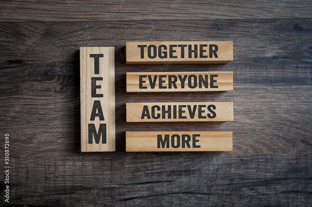 Fototapeta Wooden pieces with Team - Together everyone achieves more on wooden background