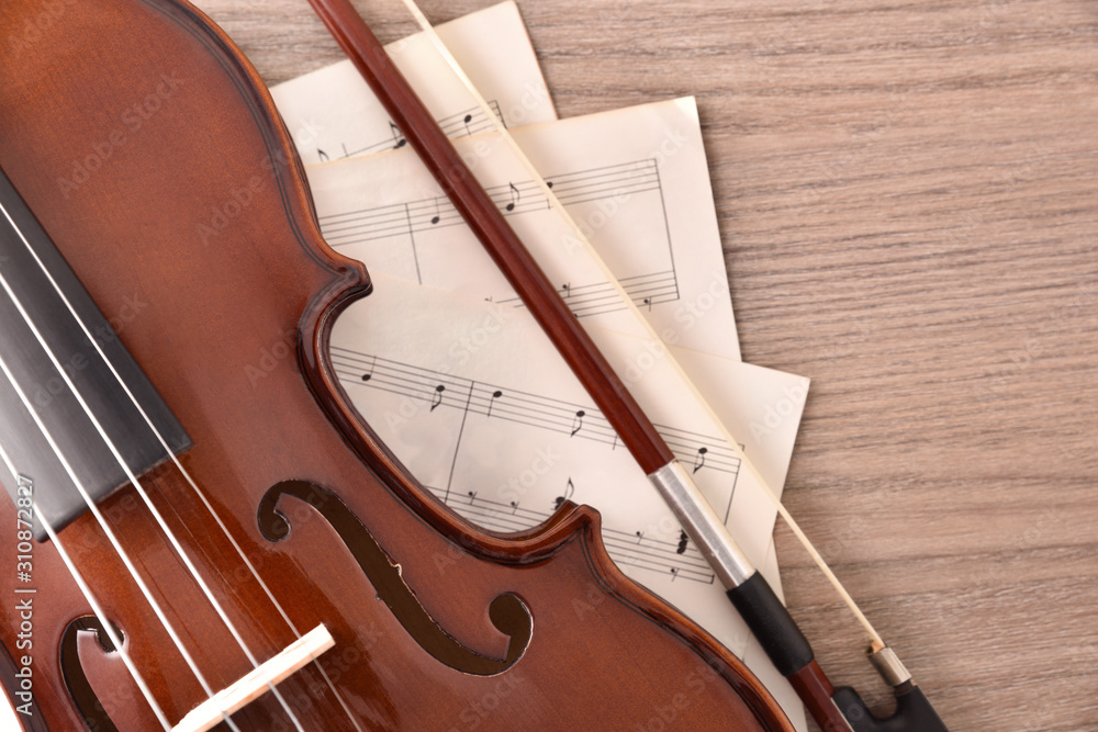 Fototapeta Violin body and bow with sheet music on wood table