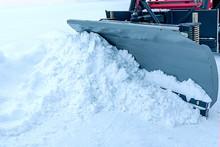 A Snowplow Bucket Pushes A Pil...