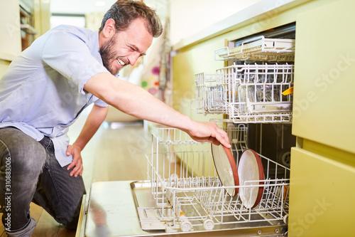Vászonkép Mann als Hausmann an der Geschirrspülmaschine