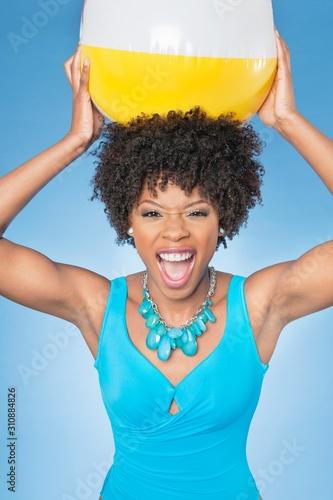 Fényképezés Attractive African American woman holding beach ball aloft over colored backgrou