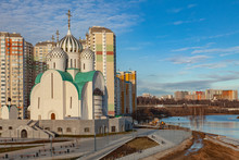 An Unusual Orthodox Church Under Construction Stands On The River Bank Against The Background Of High-rise Apartment Buildings