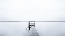 Foggy Scenery Of A Pier Leading To The Ocean On A Cold Morning