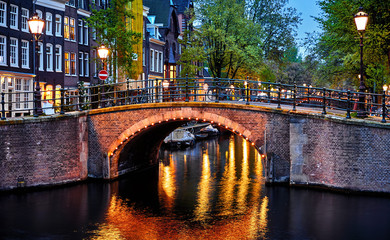 Fototapeta Uliczki Amsterdam, Netherlands. Bridges with nighttime illumination over canals with water in Old town. Quarter with traditional dutch houses. Vertical evening landscape. Blue hour.