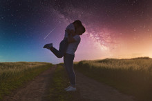 Silhouettes Of A Young Couple In Love Under The Starry Sky With Milky Way.