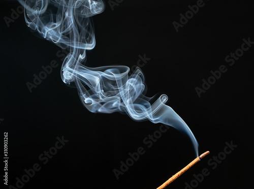 Stampa su Tela Burning incense stick with smoke on black background.