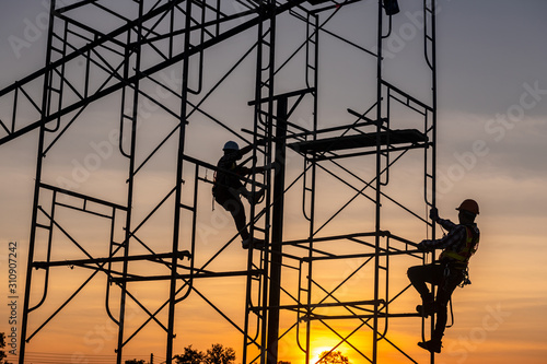 Fotografia Silhouette of engineer and construction team working safely on scaffolding on high rise building