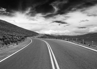 Black and white empty road into the mountains under a dramatic sky