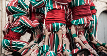 People Working As A Team Building A Human Tower