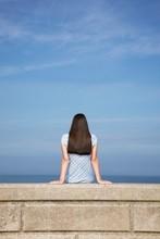 Woman Sitting On Stone Ledge At Beach