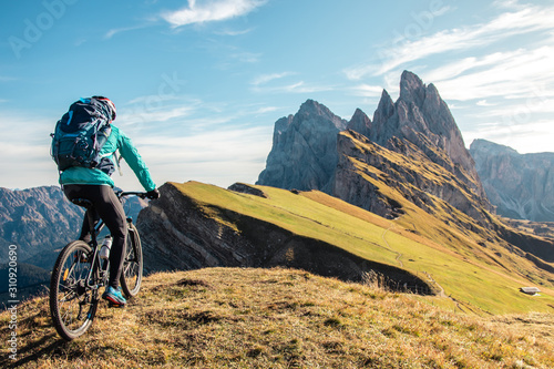 Photo Young man with mountain bike cycling on Seceda mountain peak at sunrise