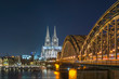 Illuminated Cologne Cathedral and Hohenzollern Bridge at night