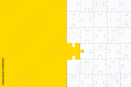 Photo Unfinished white jigsaw puzzle pieces on yellow background