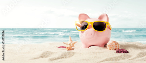 Fotografia Piggy bank on vacation. Finance and travel concept