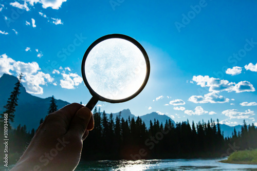 Photo man holding a magnifying glass over a bright blue sky with scattered clouds dur