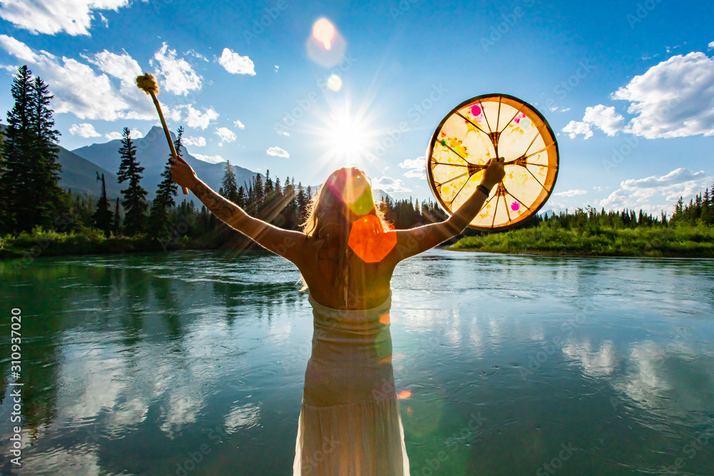 Fototapeta A backlit and rear view of a spiritual woman holding a powwow drum during a mindful ritual in nature, bright sun gives atmospheric mystical lens flare