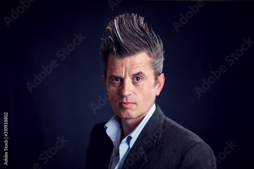Photo Man with mohawk wearing suit in front of black background.