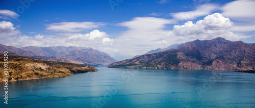 Photo Picturesque landscape and lake, Charvak reservoir, mountains background