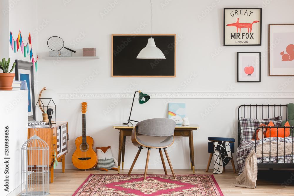 Fototapeta Stylish desk and chair in workspace in vintage genderless kid room
