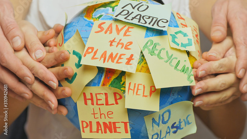 Family hands hug Earth globe with stickers with the message Save the Planet, Help and No Plastic Canvas Print