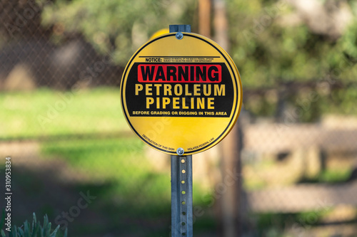 Photo Petroleum pipeline warning sign with chain link fence and in background