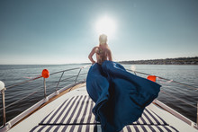 Woman In Flying Beautiful Blue Dress On A Boat. Wide View On Front Of Yacht. Back View