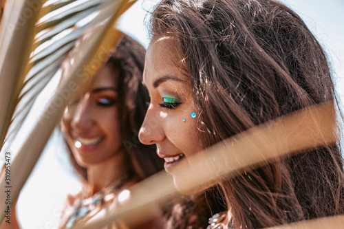 Photo close up portrait of two beautiful twin woman sisters on the beach