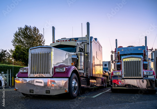 Fototapeta Big rigs classic bonnet semi trucks standing in row on truck stop parking lot at