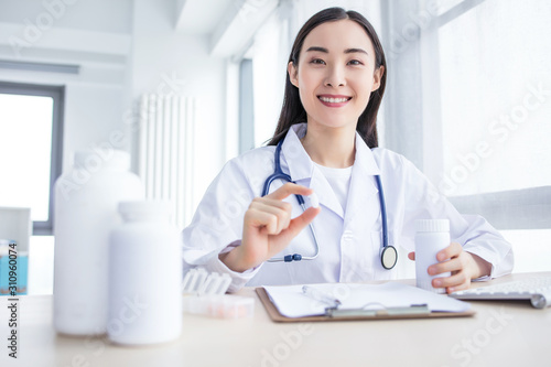 Valokuvatapetti Beautiful female physician medicine doctor or pharmacist sitting at worktable, holding jar of pills in hands and writing prescription on special form