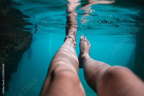 Underwater cave photo with woman's legs under surface, relaxing, swimming in tur Wallpaper Mural
