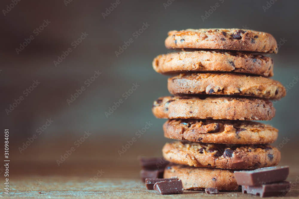 Fototapeta Chocolate chips cookies with crumbs on wooden background, homemade sweet and dessert concept