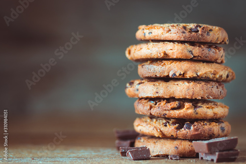 Chocolate chips cookies with crumbs on wooden background, homemade sweet and des Canvas Print