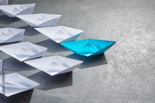 Business Concept, Paper Boat, the key opinion Leader, the concept of influence. One blue paper boat as the Leader, leading in the direction of the white ships on a gray concrete background,copy space