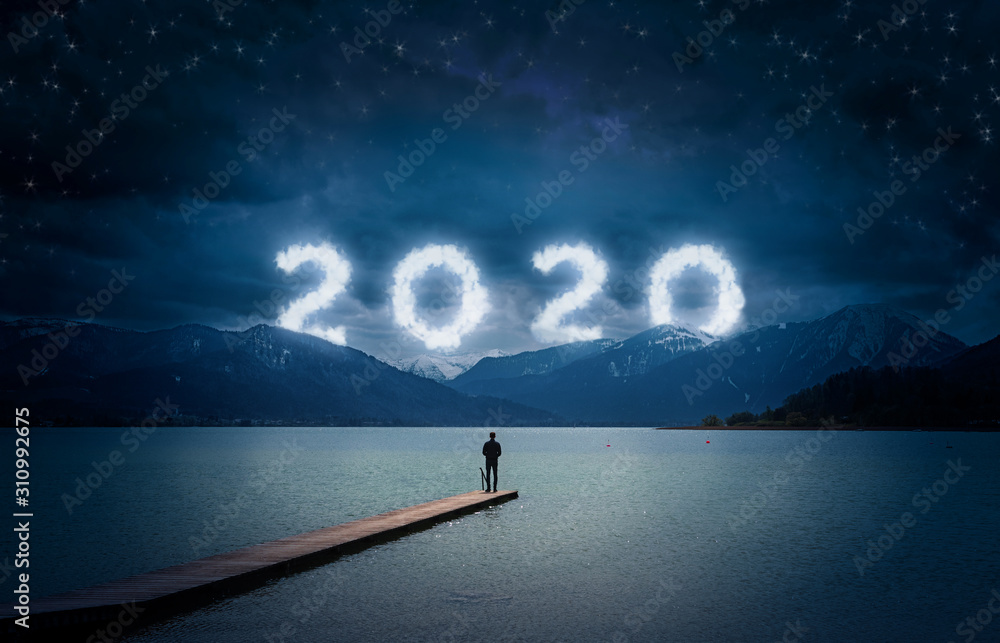 Fototapeta New year background, young man standing on a jetty in a lake and looking to the mountains under the dark sky with cloudy text 2020
