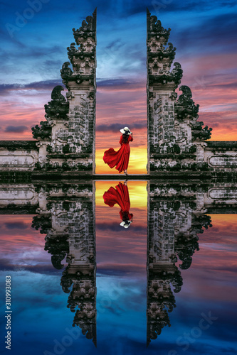 Young woman standing in temple gates at Lempuyang Luhur temple in Bali, Indonesia. Wall mural