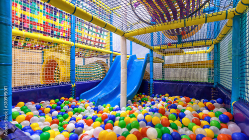 Children playground indoor. Nice plastic gym for activity in playroom. Panorama inside the plastic dry pool with colorful balls and slide.