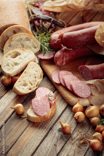 Photo  On a old wooden table sausage with bread, rosemary, onion and pepper