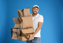 Emotional Courier With Damaged Cardboard Boxes On Blue Background. Poor Quality Delivery Service