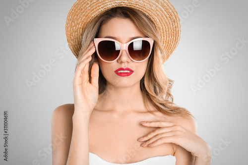 Fotografiet Young woman wearing stylish sunglasses and hat on light grey background