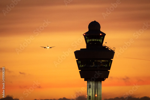 Amsterdam Schiphol International Airport control tower with a plane landing in the background during sunset Wallpaper Mural
